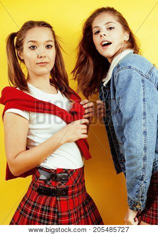 lifestyle people concept: two pretty young school teenage girls having fun happy smiling on yellow background close up