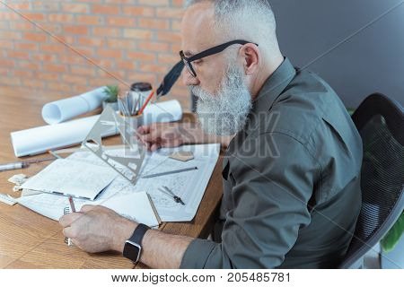 Profile of qualified mature architect is working on his project with concentration. He is sitting at table in his office and holding stencil while writing down in copybook