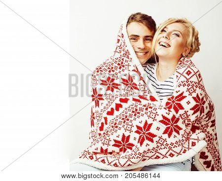 young pretty teenage couple at Christmas time warming in red decorated blanket, hipster guy with his girlfriend happy smiling and hugging isolated on white background, lifestyle people concept close up