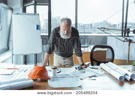 Searching for solution. Serious professional planner is leaning on desk and looking at blueprints with concentration while standing in big room
