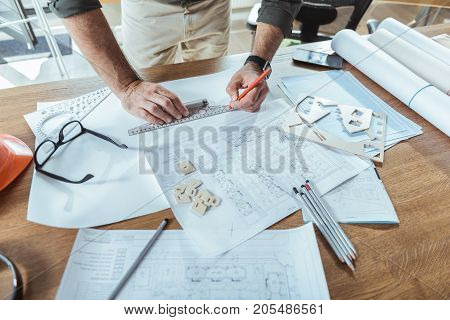 Be precise. Top view close up of working place of professional engineer who is drawing blueprint using ruler and pencil. He is standing near wooden table with his projects, glasses, mobile phone. Copy space