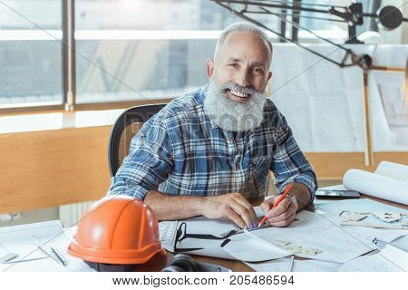 Favorite job. Portrait of happy gray-haired senior engineer with beard is sitting at table with safety helmet and working on design plan. He is looking at camera with smile