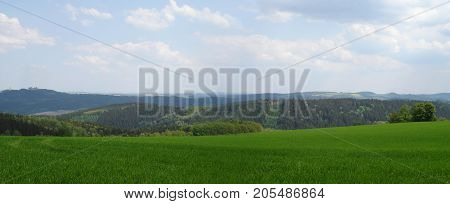panoramic of the Erzgebirge in spring; view to the Augustusburg castle, mountains and valleys, hilly landscape in Saxony, Germany