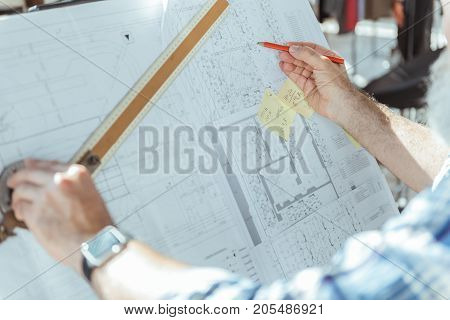 Important task. Close-up of arms of male, who is using professional equipment for making blueprints. Man is standing near drawing board and left hand holding ruler and other one pencil