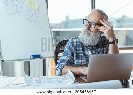 Dreaming of future. Pleasant bearded senior man is sitting at table and looking aside thoughtfully while working on laptop. He is leaning his elbow on desk and touching his head wistfully. Copy space