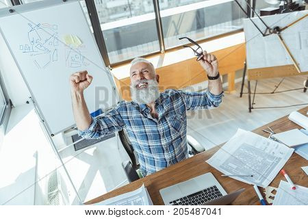 Happy moment. Top view of joyful bearded engineer is sitting at table with laptop and blueprints and expressing gladness. He is raising his hands and looking up with smile