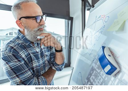 Visual materials. Stylish old bearded engineer in glasses is standing near flip chart and touching his chin while looking at board thoughtfully. Copy space in the right side