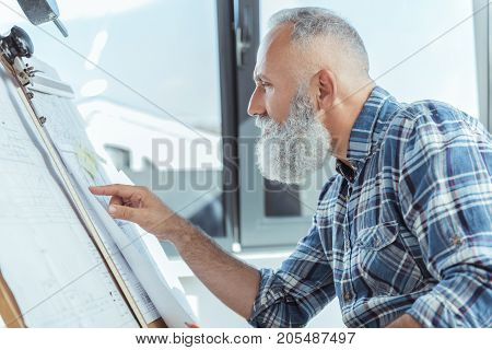 What is this. Profile of serious skillful bearded architect is pointing on blueprint while looking at document with concentration. He is sitting against window