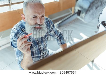 Check again. Top view of pleasant experienced bearded engineer is sitting with pencil in hand in front of board and looking at it while frowning his brows. Copy space in the right side