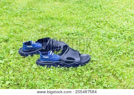 Men's rubber slippers and infant shoes are on lawn
