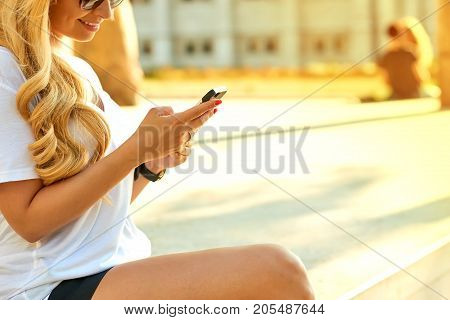 Close up look of the hands of a young woman who is holding and using her smartphone