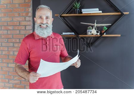 Successful and stylish. Cheerful old gray-haired man is standing with documents and expressing happiness while looking at camera with joy. Copy space in the right side