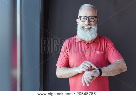 What time. Portrait of cheerful old bearded man in glasses is pointing on his watch with wide smile while looking at camera with joy. Copy space in the left side