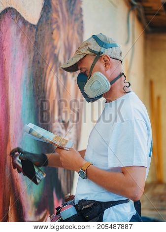 Graffiti Artist Painting On The Street Wall. Man with aerosol spray bottle near the wall. Young talented guy in protective mask drawing colorful lion.
