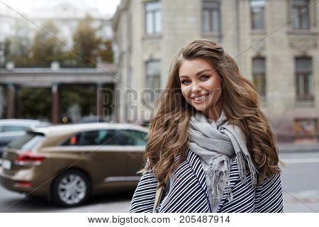 Beautiful cheerful young lady with voluminous hair wearing stylish coat and scarf posing on city street on her way to store having joyful happy look enjoying warm spring day. People and lifestyle