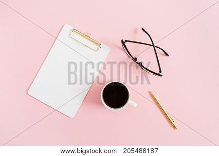 Minimal women home office desktop with clipboard pen coffee mug and glasses on pink background. Flat lay top view blog header or hero.