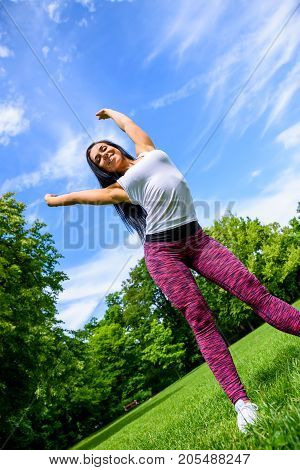 A beautiful young sporty girl throwing her hands up happily on a field in a park