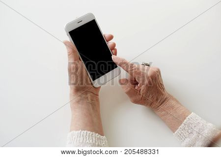 People technology job occupation and age. Close up shot of senior woman hands holding smart phone with copy space. Modern retired elderly female using wifi on mobile earning money via internet