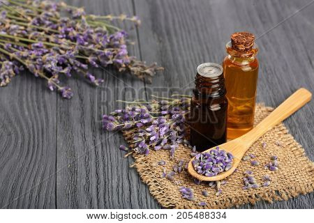 Herbal oil and lavender flowers on wooden background.