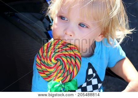 Toddler Eating A Yummy Colorful Lollipop. Baby Boy With Swirl Lollipop