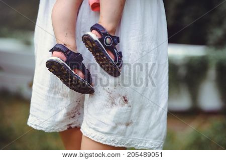 shod feet of a child in the arms of a mother a white dress stained with shoes raising children and loving them.