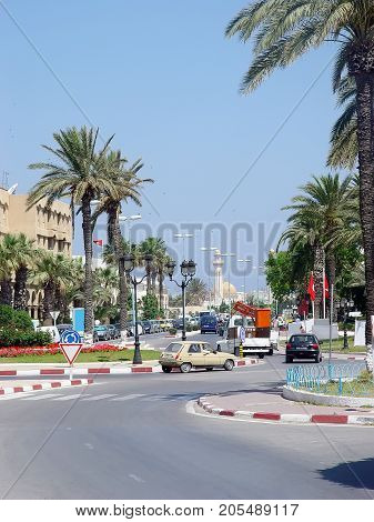 Street of the city of Monastir with palm trees and minarets. Tunisia