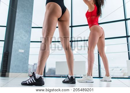 Close-up image of sexy sporty slim female butts and legs in swimwear and trainers in gym.