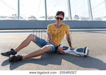 Full length portrait of cheerful young man having rest outdoor. He sitting on asphalt near giroscooter while looking at camera