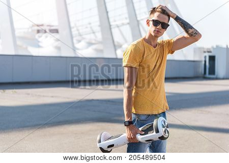 Portrait of calm young man touching to hairs by arm while holding gyroscope. He looking at camera. Technology concept. Copy space
