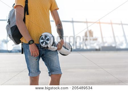 Close up young man hand holding new gyroboard in hand while walking at street. Copy space
