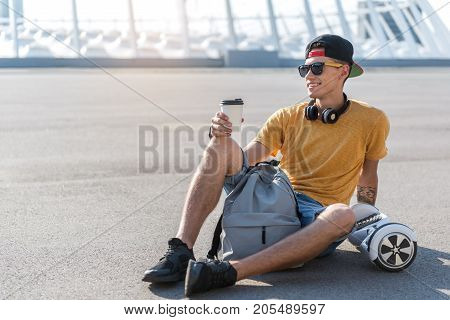 Full length side view smiling teenager having rest near gyroboard at street. He sitting on ground while drinking cup of coffee. Pleasure concept. Copy space