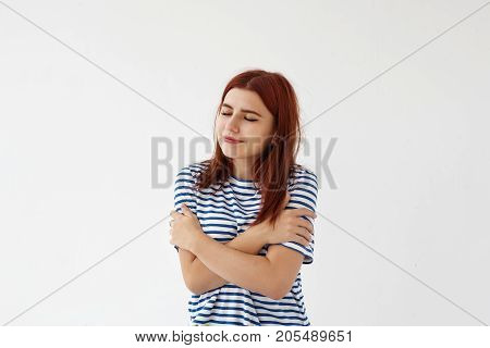 Studio shot of relaxed happy young female wearing winged eyeliner closing her eyes and hugging herself having pleased joyful facial expression. Self-love and self-esteem concept. Body language