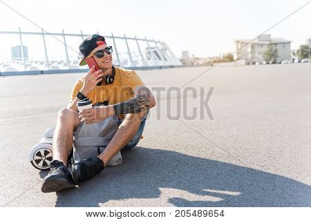 Portrait of beaming boy telling by mobile while sitting on asphalt and tasting mug of beverage at street. Copy space