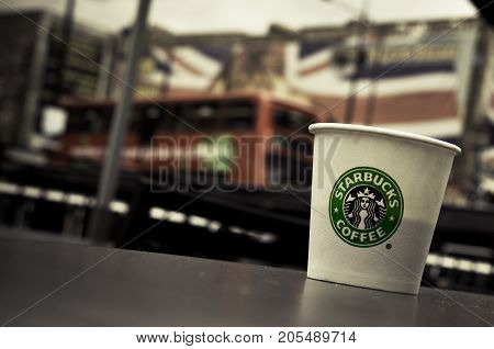LONDON, UK - OCTOBER 13, 2009 - A Starbucks paper coffee cup on a table in Camden Town, London bus and Union Jack on background.