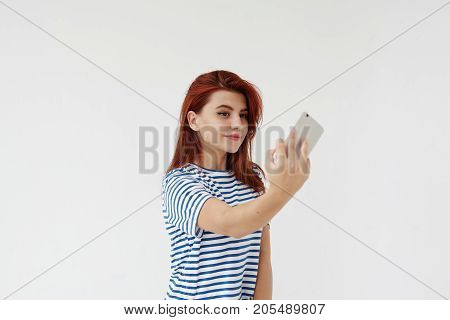 Positive charming young Caucasian woman with red hair and make up smiling while taking selfie using mobile phone. Pretty teenage girl with cute smile posting self portrait via social networks