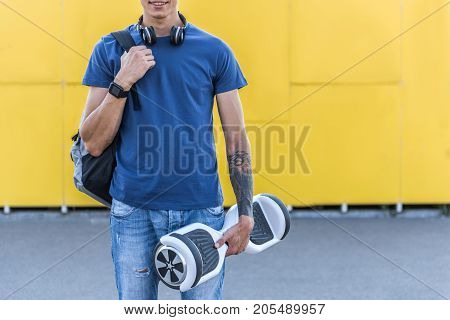 Smiling young student keeping big bag and modern gyroscope in hand. Copy space