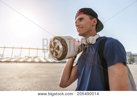 Low angle cheerful teenager holding hoverboard at street. Copy space