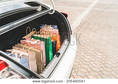 Shopping bags in car trunk or hatchback with copy space. Modern shopping lifestyle rich people or leisure activity concept