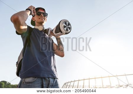 Low angle portrait of beaming teenager holding hoverboard at street. Technology concept. Copy space