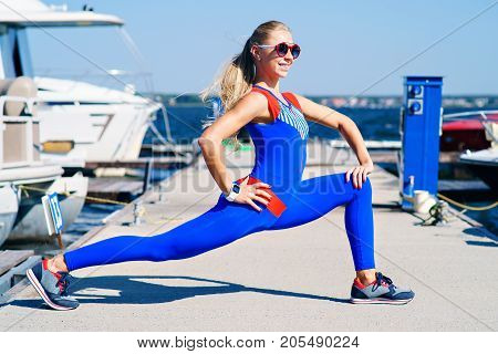 Fitness girl is engaged on the dock in a blue suit against the background of yachts