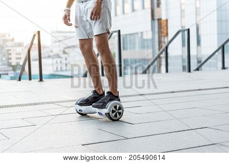 Close up male legs moving on gyroscope at street. Technology concept