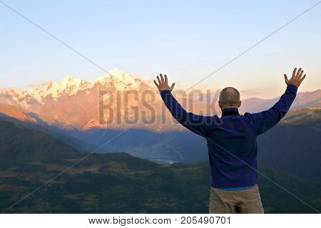 man with and raised hands standing in front of the mountains