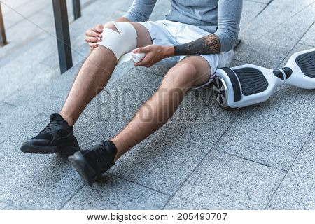 Close up man legs. He bandaging them while sitting on floor outdoor near gyroscooter