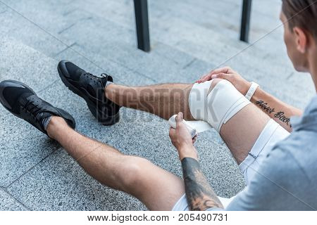 Top view close up man bandaging leg on floor outdoor. Injury concept