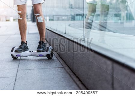 Close up injuring man feet situating on gyroscope near glass case. They mirroring in it. Technology concept. Copy space