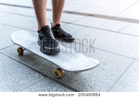 Close up man going on board on asphalt outdoor. Entertainment concept