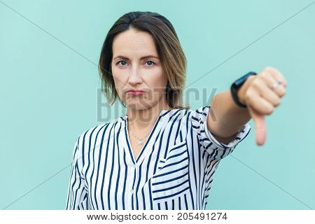 Portrait Of Unsatisfied Sensual Lady With Thumbs Down And White Shirt Against Light Blue Background.