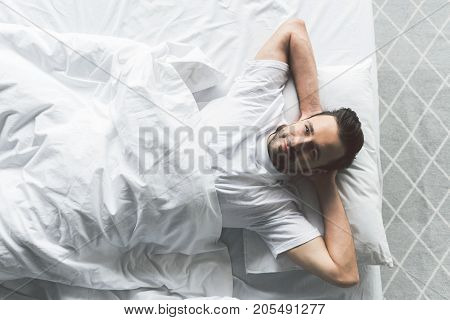 It is great to wake up in the morning. Top view portrait of handsome guy lying on white bedding and looking at camera with happiness