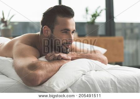 It is great to wake up at home. Side view profile of dreamful young man lying on bed and relaxing. He is looking forward with cute smile. Copy space