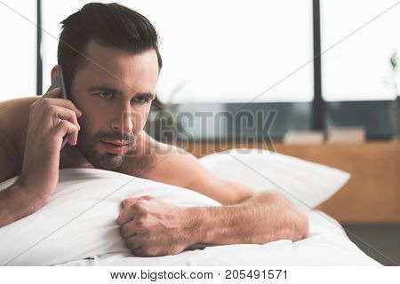 Bad news. Portrait of serious young man speaking by cellphone after waking up. He is lying on bed and looking forward pensively. Copy space